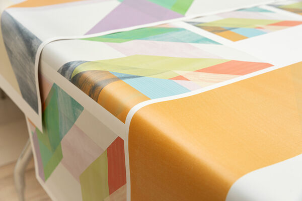Customized colourful wallcovering laid out over a table